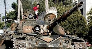 Syrian boy sits atop a damaged military tank