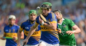 STOP ME IF YOU CAN: Tipperary's Kevin Downes evades the tackle of Limerick's Wayne McNamara in the 2012 Munster SHC quarter-final at Semple Stadium. Picture: Barry Cregg/Sportsfile