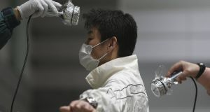 A man is screened for radiation contamination at an evacuation shelter in Koriyama, Fukushima prefecture, Japan today.
