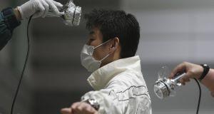 A man is screened for radiation contamination at an evacuation shelter in Koriyama, Fukushima prefecture, Japan today.