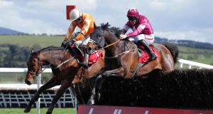 Twinlight ridden by Ruby Walsh (left) jumps ahead of Far Away So Close ridden by Davy Russell to win the second race of the day yesterday. Picture: INPHO/Donall Farmer